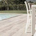 En terrass med pool och träklinker från Pronto kakel AB